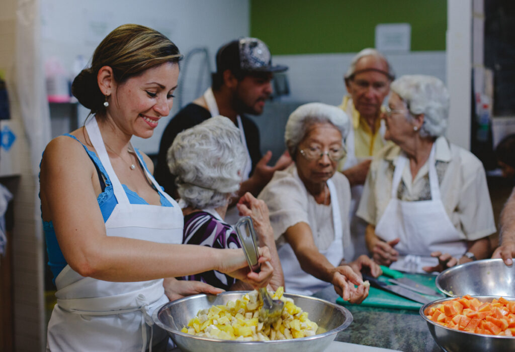 A group cooks together in our Community Kitchen, with a smiling woman in the foreground