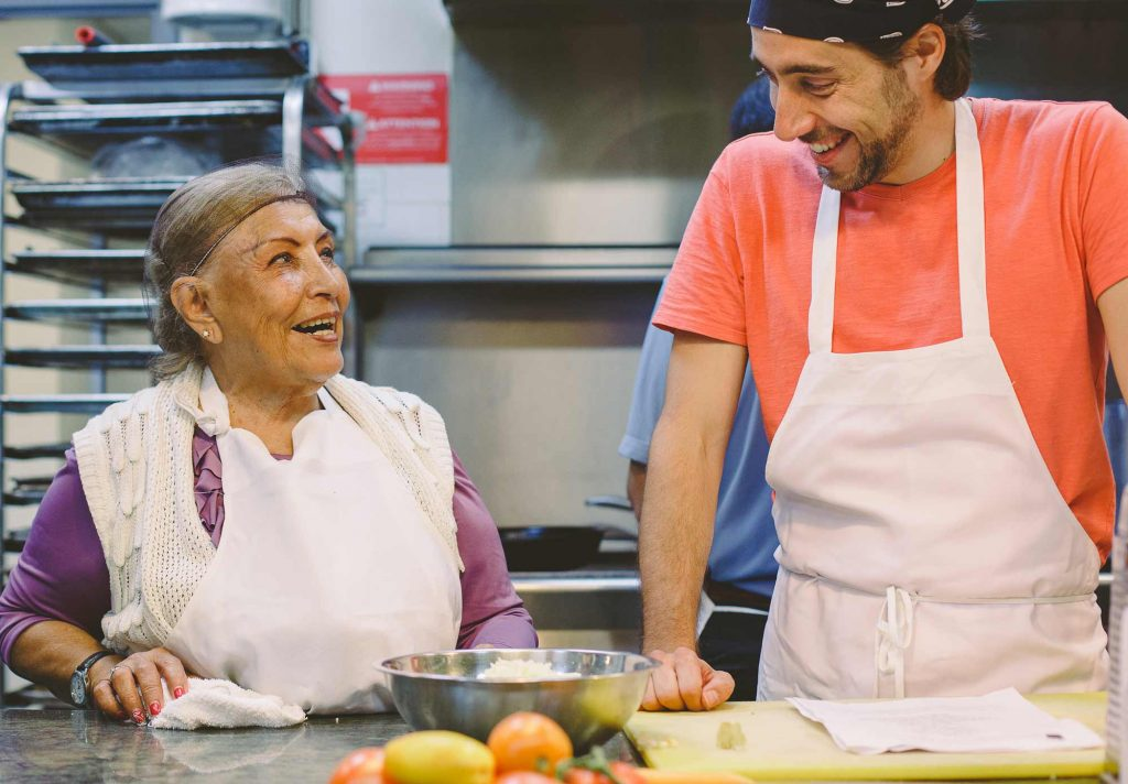 A senior woman and young man laugh together in a Community Kitchen